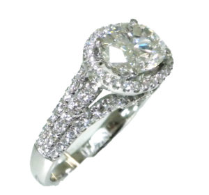 Horizontally set oval-cut diamond that is surrounded in a hallo of micro-pave set full-cut round diamonds that is accompanied by an 18k white gold shank; it is constructed from three wires, all three are pave-set with full-cut round diamonds.