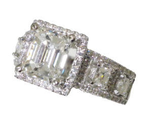 Emerald-cut diamond that is surrounded with a hallo of micro-pave set full-cut round diamonds and whose shoulders of 18k white gold are embellished with micro-pave full-cut round diamonds that displays four asher-cut diamonds.
