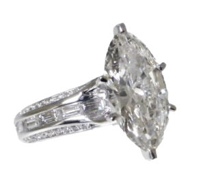 """Marquise-cut daimond set in a six-prong """"Tiffany"""" setting that is showcased by an 18k white gold shank of micro-pave set full-cut round diamonds and channel-set straight baguette diamonds."""